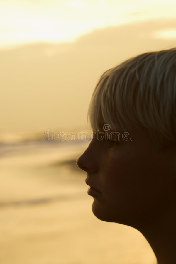 Boy on beach at sunset stock image
