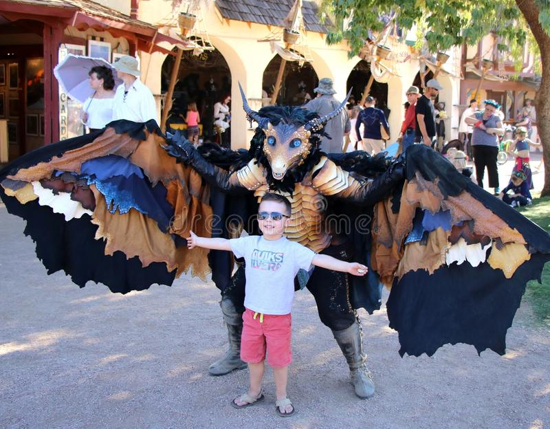Boy and a Beautiful Creature. A street performer dressed as a beautiful dragon looking creature is taking a picture with a boy at the Renaissance Fair held in royalty free stock photos