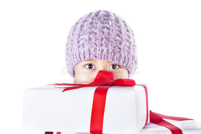 Boy behind Christmas gifts isolated in white. Boy with beany is hiding behind christmas gifts , isolated in white royalty free stock images