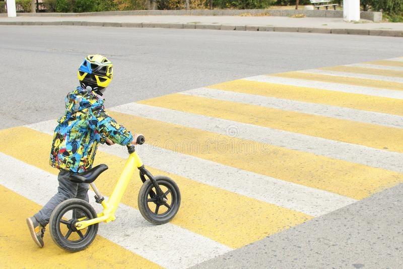 A boy with a bicycle crosses a pedestrian crossing with yellow markings. Traffic rules stock photos