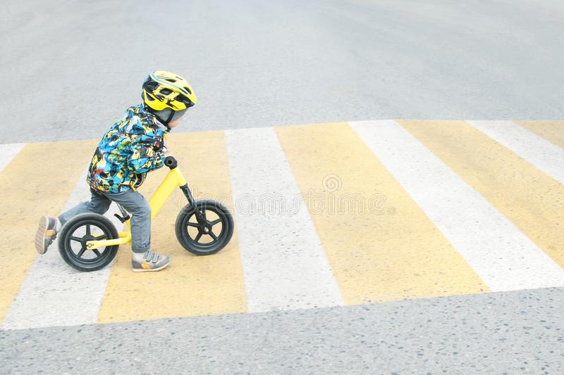 A boy with a bicycle crosses a pedestrian crossing with yellow markings. Traffic rules royalty free stock photos