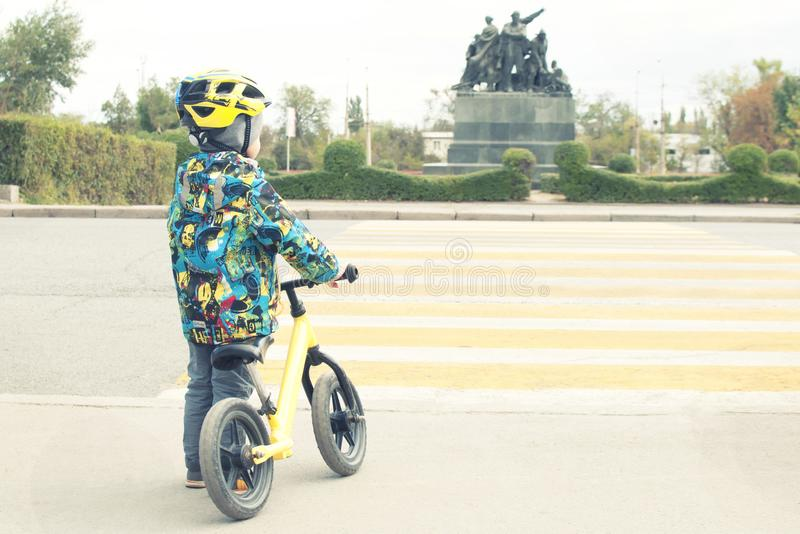 A boy with a bicycle crosses a pedestrian crossing with yellow markings. Traffic rules stock image