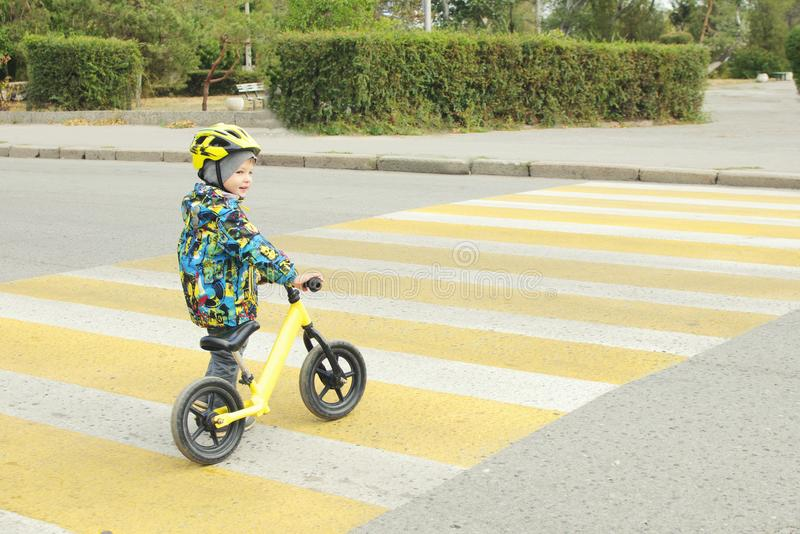 A boy with a bicycle crosses a pedestrian crossing with yellow markings. Traffic rules stock images