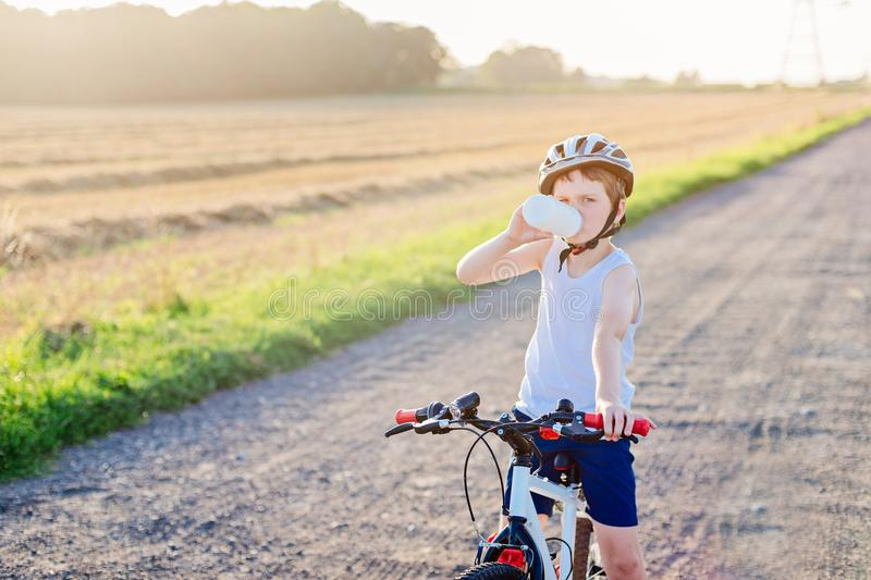Boy in a bicycle helmet drinks bottled water. Child on bike stock photography