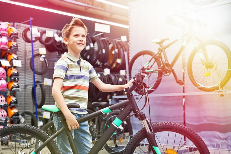 Boy and bicycle in sport shop stock image