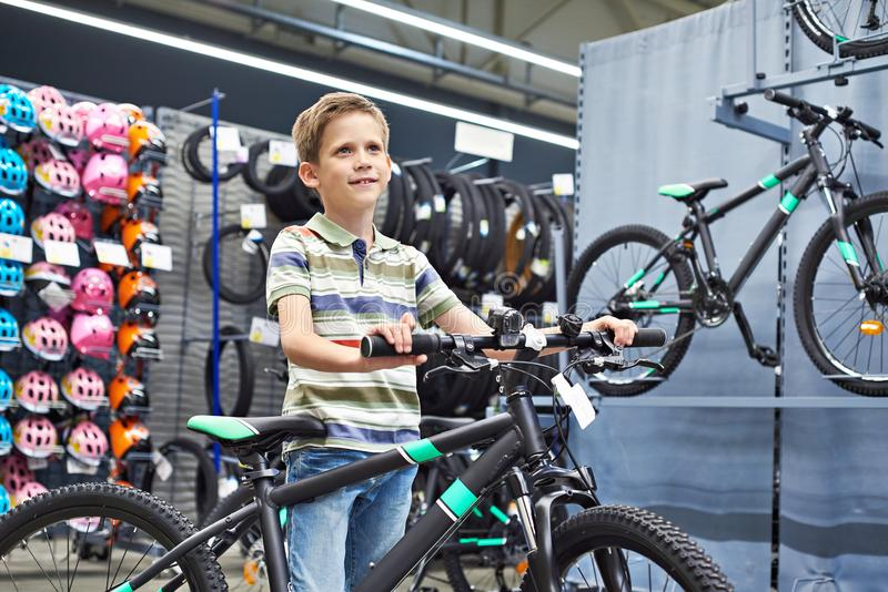 Boy and bicycle in sport shop stock photography