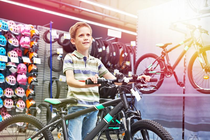 Boy and bicycle in sport shop stock photo
