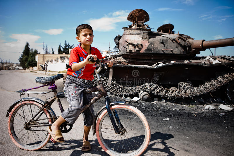Boy and bicycle with T72 tank, Azaz,Syria. stock photo