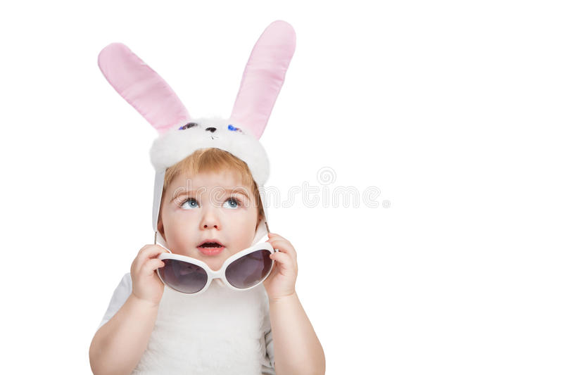 Boy with big blue eyes dressed in Easter bunny ears take off sunglasses and looking up. Little Easter bunny on white background stock image