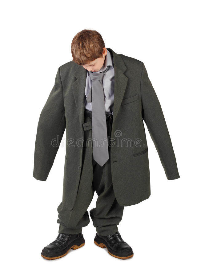 Boy in big man's suit and boots looking at floor stock photos
