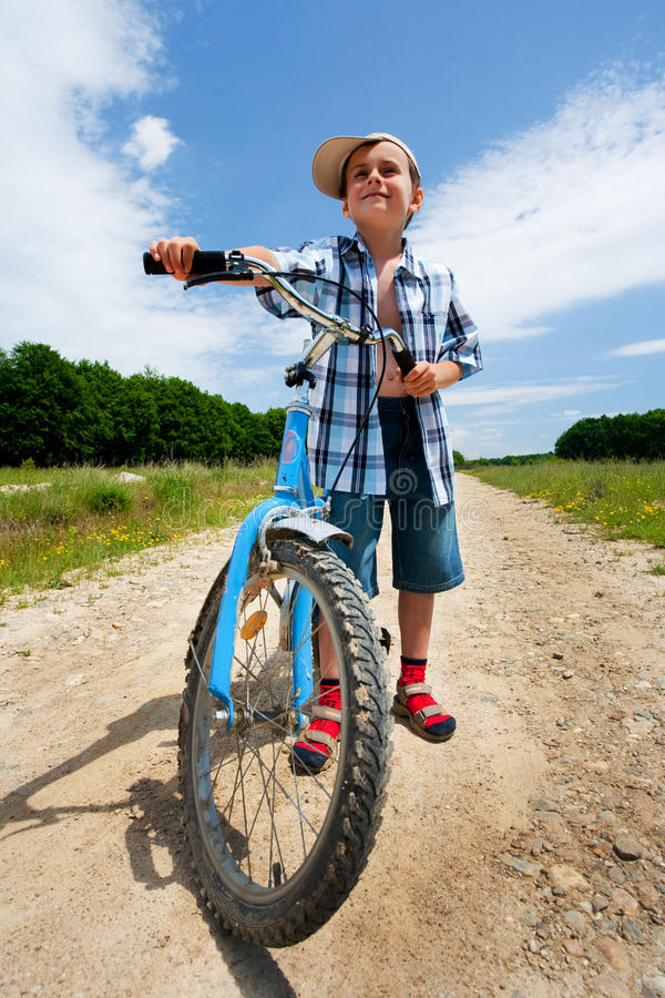 Boy with bike on a country road through meadow stock photo