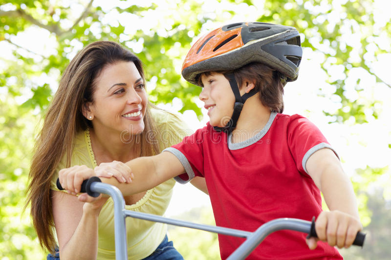 Boy on bike with mother stock photo