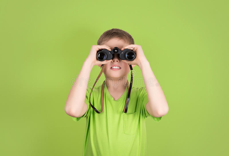 Boy with binoculars isolated on green background with copyspace. Kid looking through binoculars. royalty free stock image