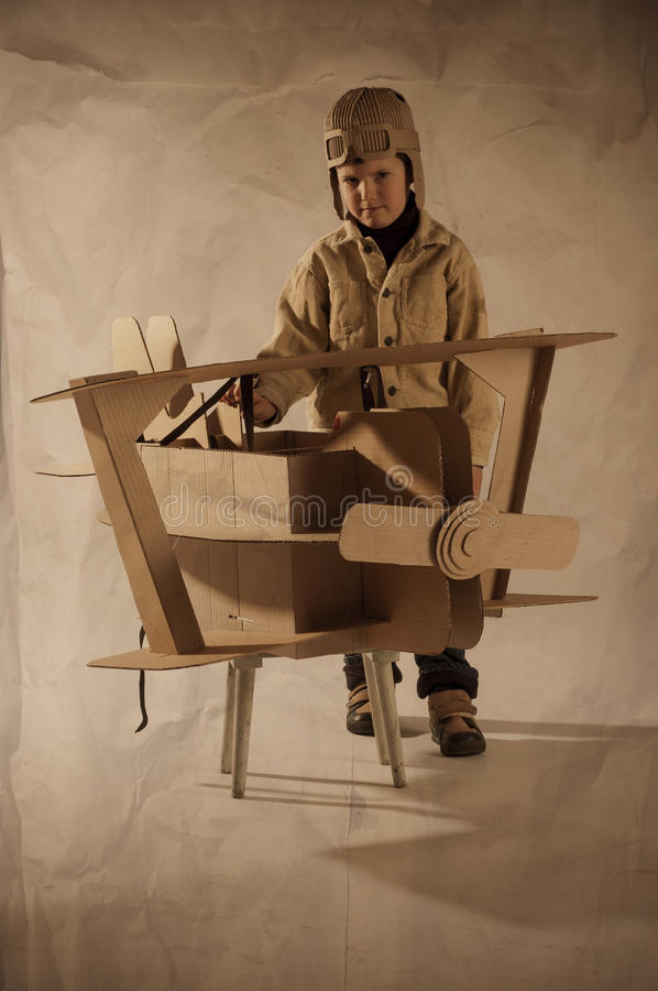 Boy and biplane. Young aviator in a homemade cardboard aircraft. biplane stock photography