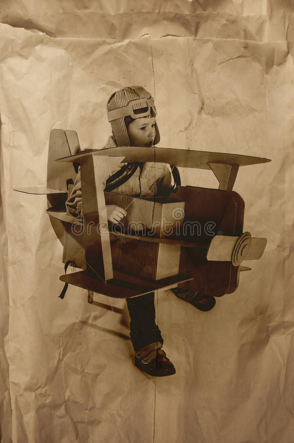 Boy and biplane. Young aviator in a homemade cardboard aircraft. biplane. photo on crumpled paper royalty free stock images