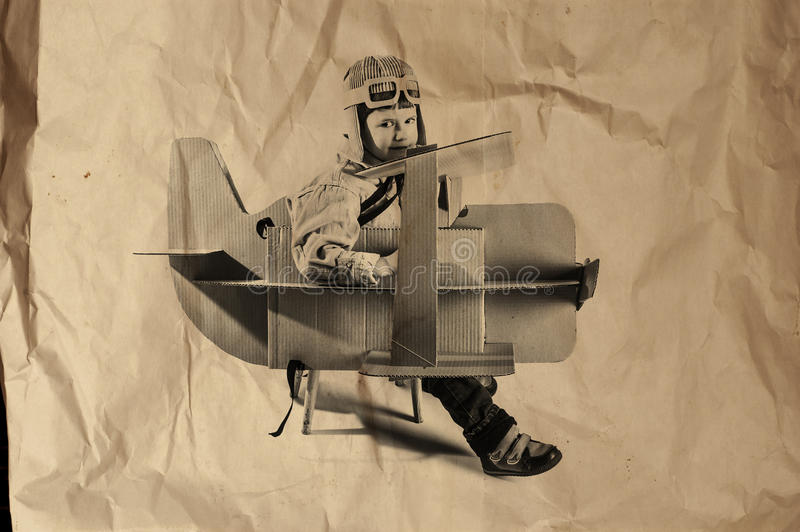 Boy and biplane. Young aviator in a homemade cardboard aircraft. biplane. photo on crumpled paper stock photos