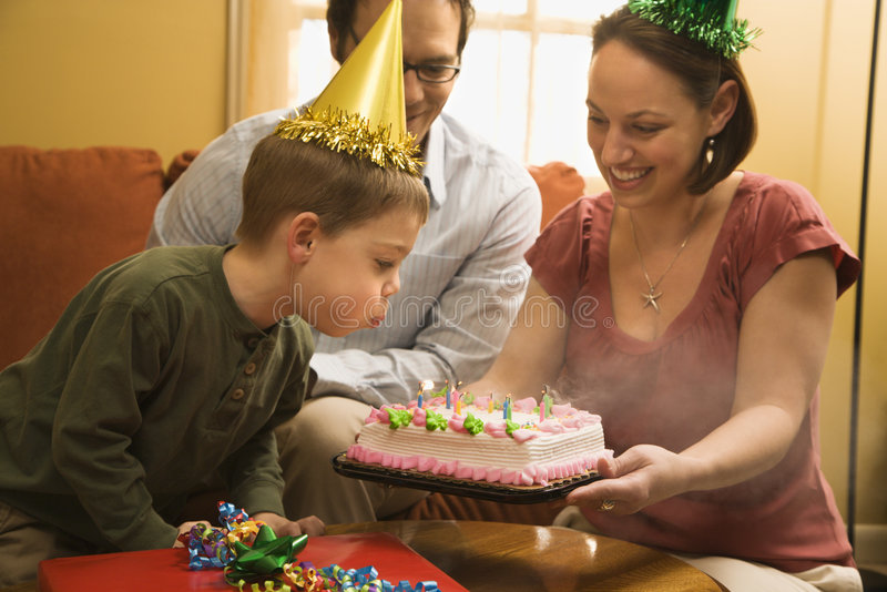 Boy with birthday cake. Caucasian boy in party hat blowing out candles on birthday cake with family watching royalty free stock photo