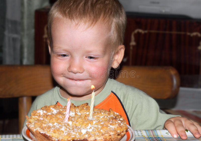 Boy with birthday cake. Two-years boy with birthday cake and candles royalty free stock image