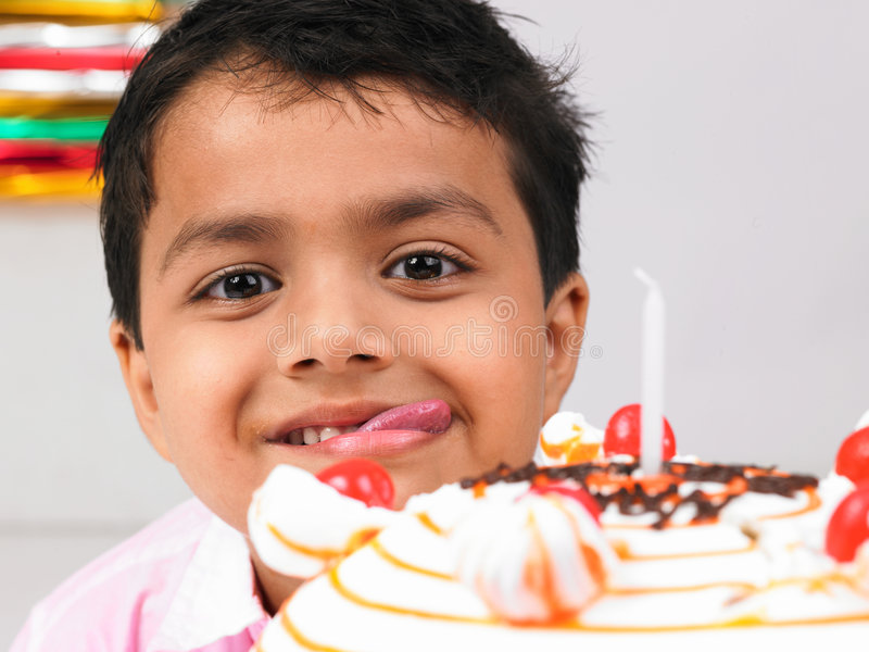 Boy with birthday cake. Asian boy with birthday cake and tounge sticking out stock photos