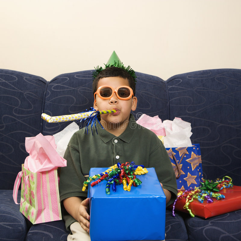 Boy and birthday party favors. Hispanic boy with birthday party favors and presents looking at viewer stock photography
