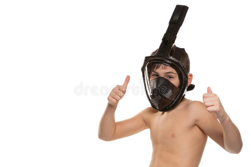 A boy in a black full face diving mask, both hands raised up and showing an affirmative gesture, on a white background, isolate royalty free stock photo
