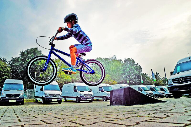 Boy in Black Nutshell Helmet on Blue Bmx Bike Having Hangtime After Taking Off on Ramp stock photography