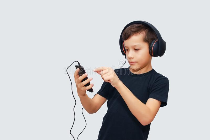 Boy in black t-shirt having fun with smartphone and headphones. Smiles royalty free stock photo