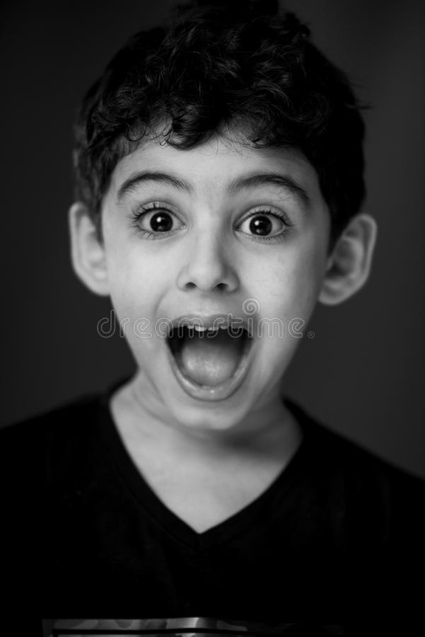 Boy in Black V-neck Shirt With Looking Straight to the Camera With a Shocking Face Expression stock photo