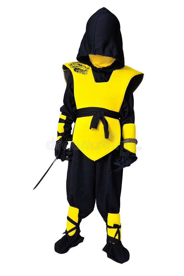 The seven-years old boy in black and yellow ninja suit with a ho. A boy in black and yellow ninja suit with a hood and mask on his face bowed his head. With a stock photos
