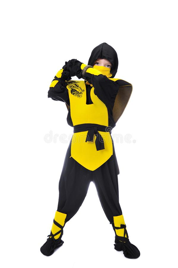 The seven-years old boy in black and yellow ninja suit with a ho royalty free stock photos