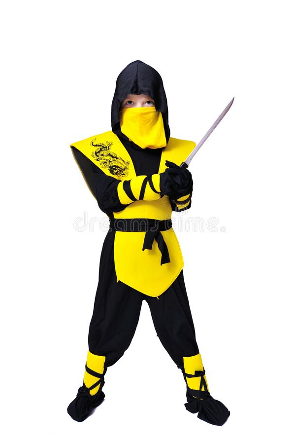 The seven-years old boy in black and yellow ninja suit with a ho royalty free stock photography