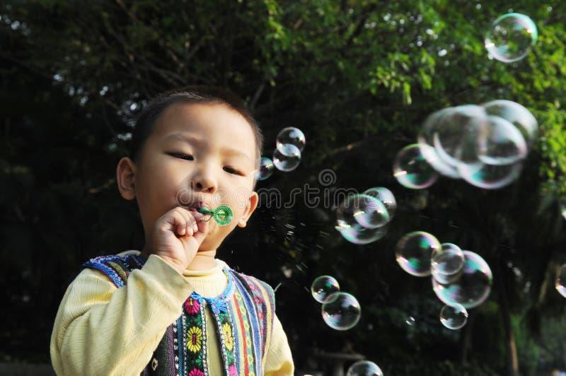 Boy blowing bubbles stock image