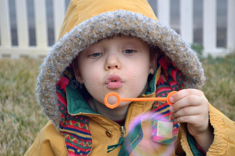Download Boy Blowing Bubbles In The Winter Stock Photo - Image of green, bubbles: 105724838