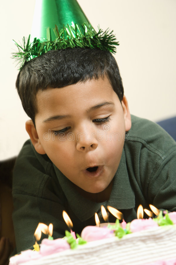 Boy blowing out candles royalty free stock photos