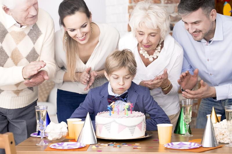 Boy blowing out candles on birthday cake royalty free stock image