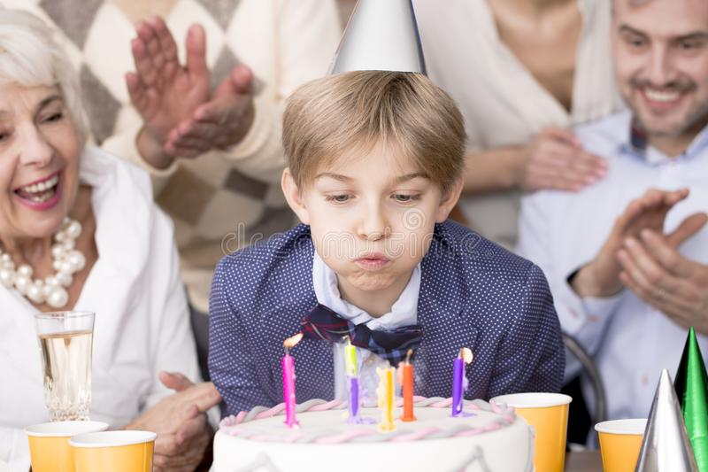 Boy blowing out candles stock images
