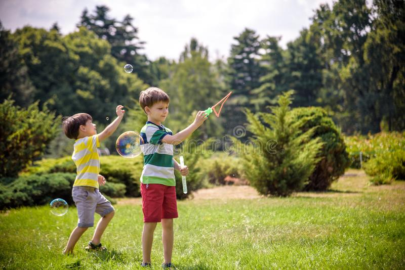 Boy blowing soap bubbles while an excited kid enjoys the bubbles. Happy teenage boy and his brother in a park enjoying making soap stock image