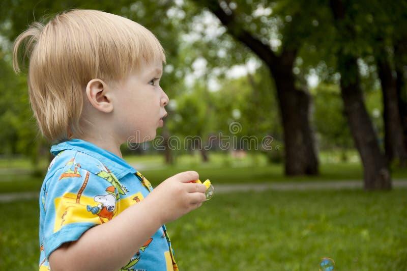 The boy blows soap bubbles stock image
