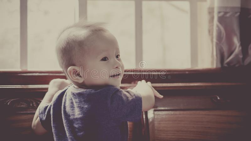 Boy in Blue Crew Neck Shirt Standing in Front of Window stock photography
