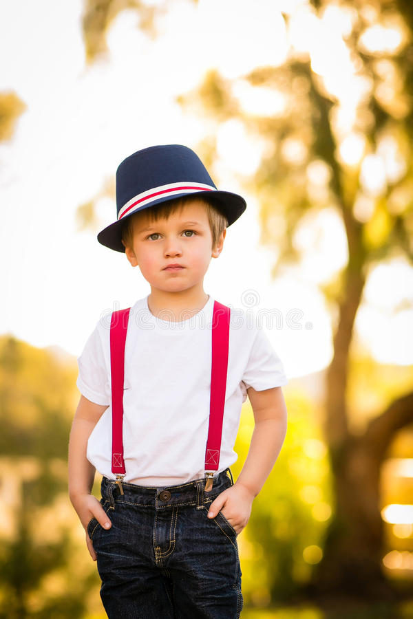 Child boy hat blue serious face. Young child in blue and red hat or fedora and red suspenders serious or stoic look on face royalty free stock images