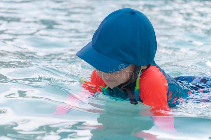 Boy with blue hat and orange suit is playing in swimming pool royalty free stock image