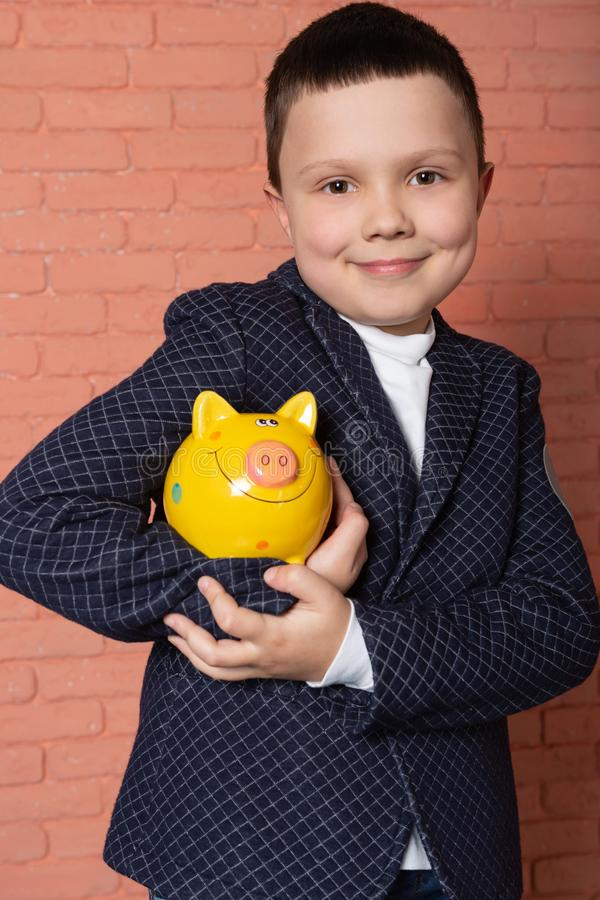 A boy in a blue jacket, holding a yellow piggy bank under his arm and smiling. concept of savings stock images