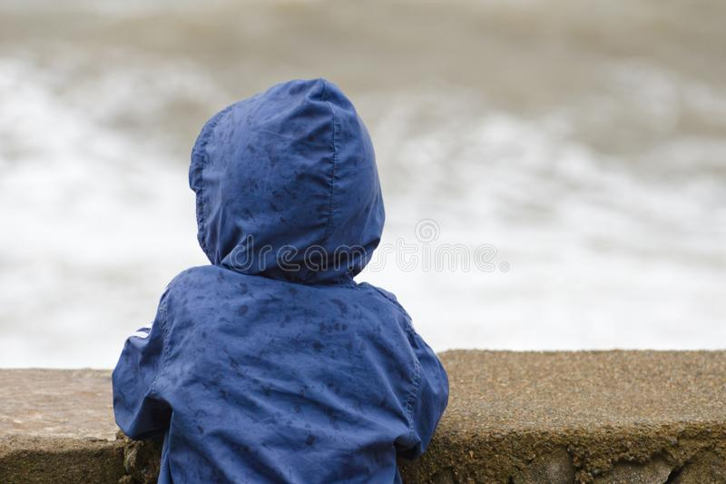 Boy in blue jacket with hood stands with his back against the pier against the background of sea waves stock images