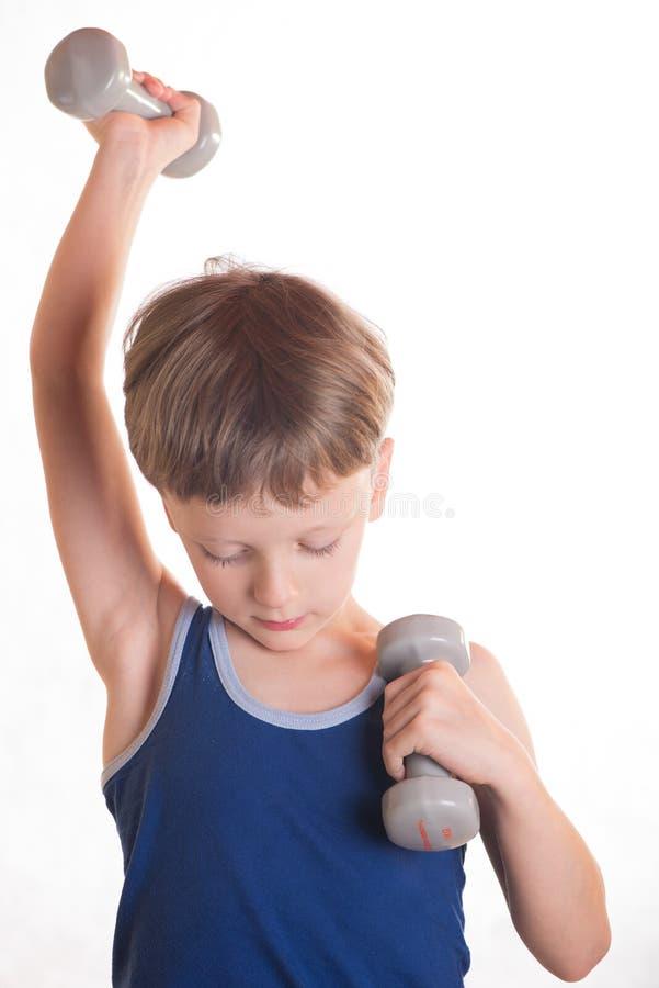 Boy blue shirt doing exercises with dumbbells over white background royalty free stock photo