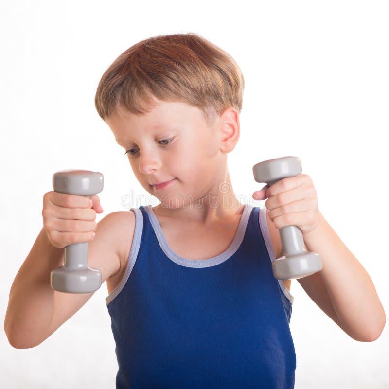 Boy blue shirt doing exercises with dumbbells over white background stock photography