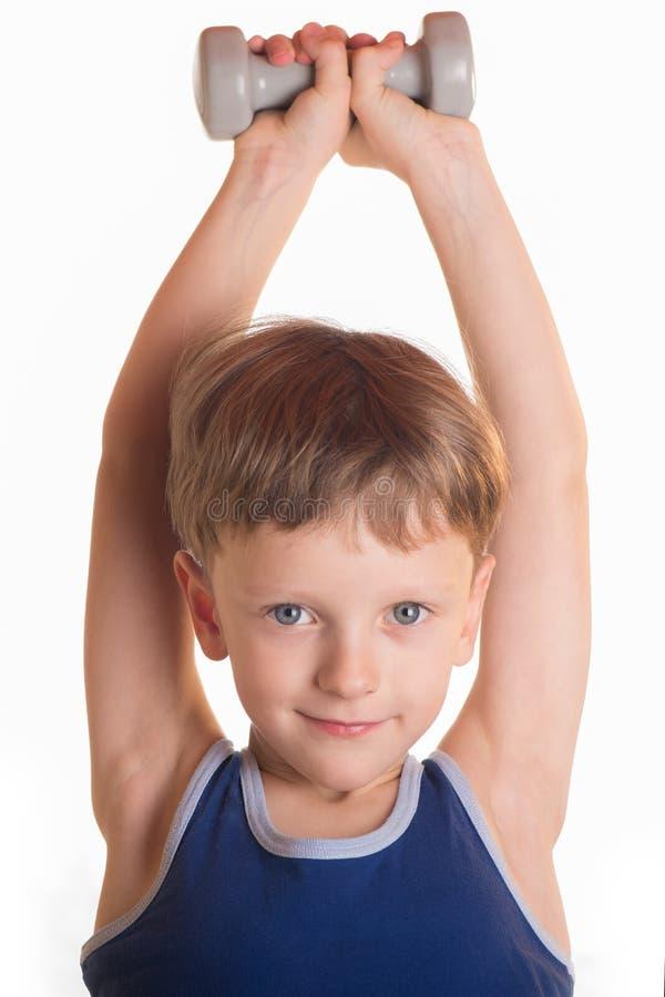 Boy blue shirt doing exercises with dumbbells over white background royalty free stock photos