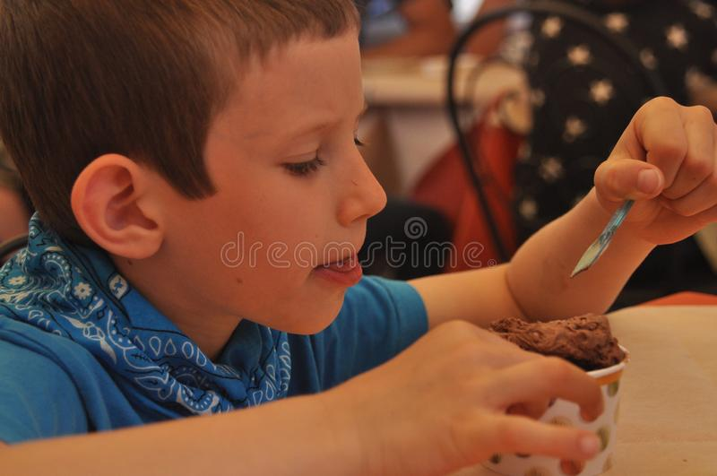 A boy in a blue shirt eating chocolate ice cream in a restaurant stock photos