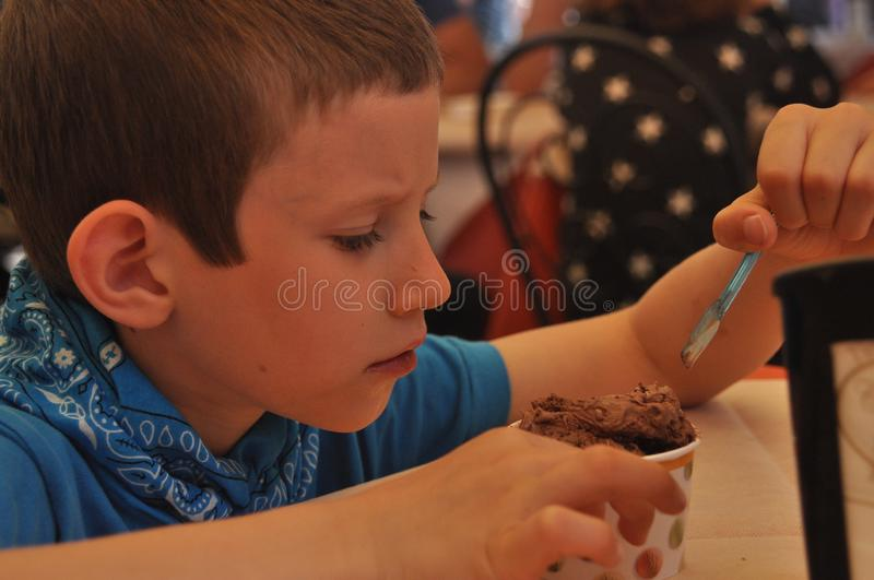 A boy in a blue shirt eating chocolate ice cream in a restaurant royalty free stock photos
