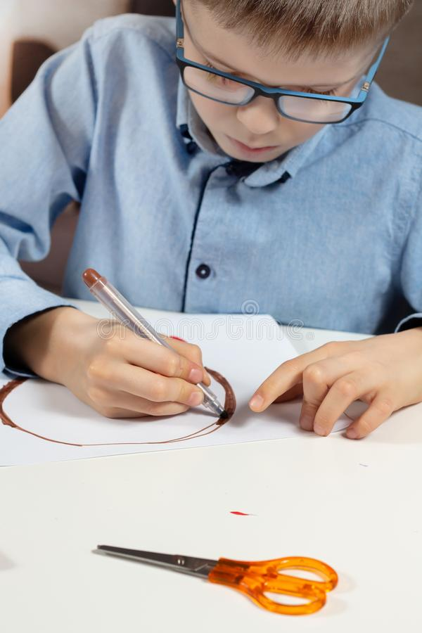 Boy in a blue shirt and glasses sits at a desk and concentrates on doing plastic work with colored paper. The boy is painting with. The boy in a blue shirt and stock images