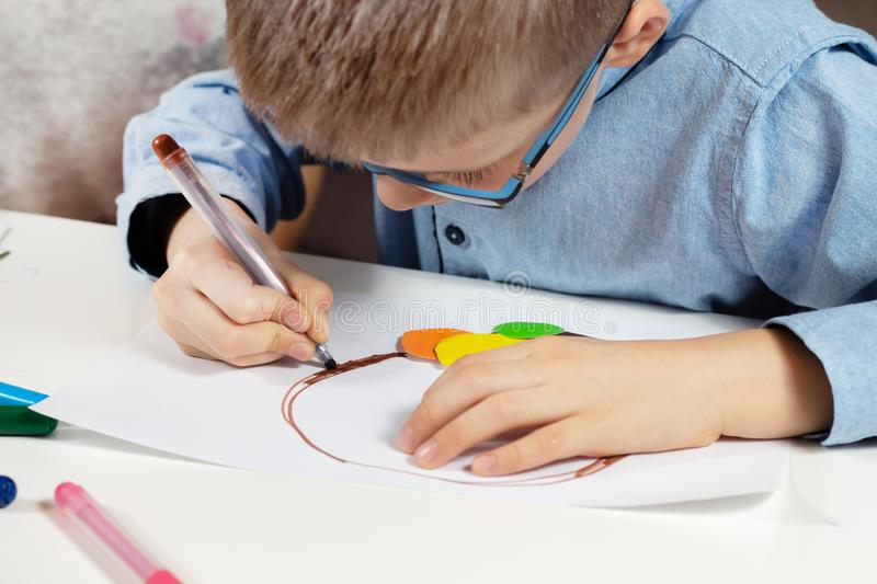 Boy in a blue shirt and glasses sits at a desk and concentrates on doing plastic work with colored paper. The boy is painting. Children`s hands hold a brown felt royalty free stock photo